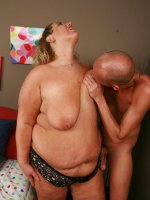 Gorgeous blonde BBW Lilly West is spread eagled and naked in bed while she gets hosed with cum