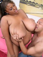 Pretty ebony fondling her huge tits while sucking cock