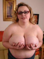 Eager blonde BBW Holli poses for the camera while getting rid of her clothes to unleash her huge rack
