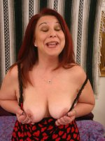Photos of a fat mature redhead named Nina being sexy and stripping off her clothes for the camera