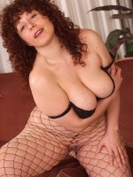 Busty brunette Yvette puts on sexy black fishnet stocking and poses nude